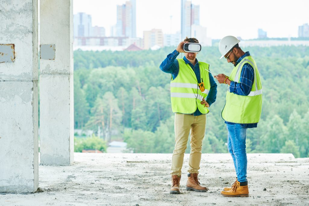 Full length portrait of two contemporary workers using VR to visualize projects on construction site, copy space